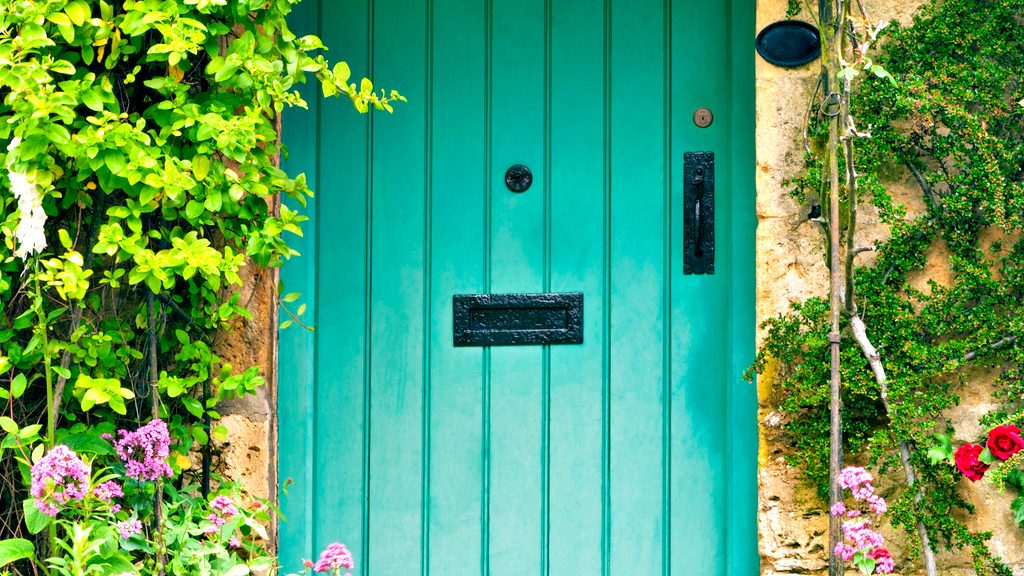 Green wooden doors in an old traditional English stone cottage surrounded by climbing red roses and flowers