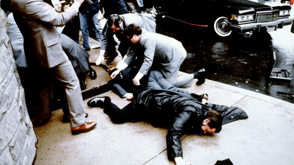 This photo taken by presidential photographer Mike Evens on March 30, 1981 shows police and Secret Service agents reacting during the assassination attempt on then US president Ronald Reagan, after a conference outside the Hilton Hotel in Washington, D.C.. Police officer Thomas Delahanty (foreground) and Press Secretary James Brady (behind) lay wounded on the ground. Reagan was hit by one of six shots fired by John Hinckley, who also seriously injured press secretary James Brady (just behind the car).  Reagan was hit in the chest and was hospitalized for 12 days. Hinckley was aquitted 21 June 1982 after a jury found him mentally unstable. / AFP PHOTO / CONSOLIDATED NEWS PICTURES / MIKE EVENS