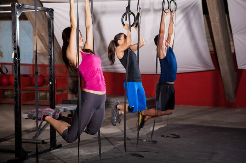 Group of three people pulling their weight up in the gymnastic rings in a gym gym