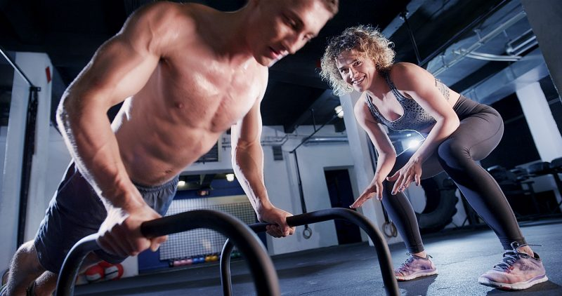 Woman personal trainer motivates a man to to effort in gym workout.