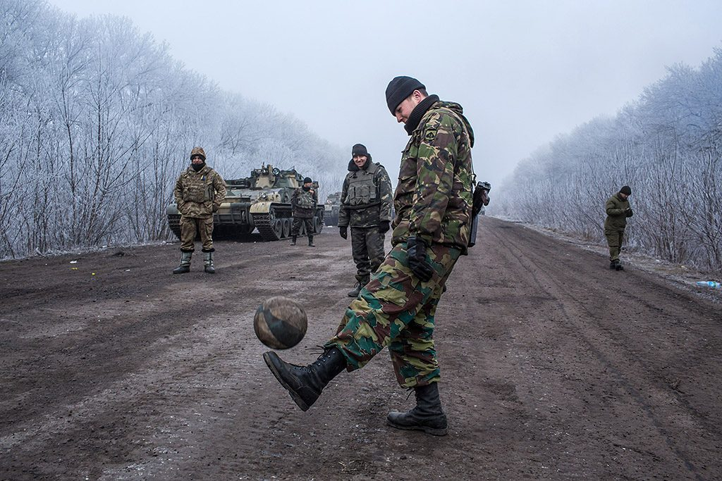 ARTEMIVSK, UKRAINE - FEBRUARY 15: Ukrainian soldiers play football on the road leading to the embattled town of Debaltseve on February 15, 2015 outside Artemivsk, Ukraine. A ceasefire scheduled to go into effect at midnight was reportedly observed along most of the front, save for near the embattled town of Debaltseve. (Photo by Brendan Hoffman/Getty Images)