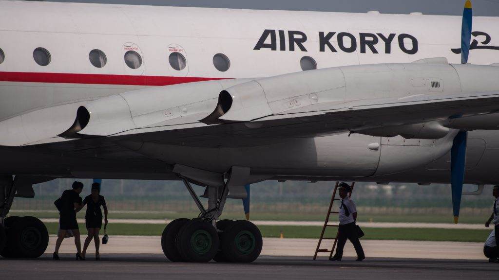 Crew members walk beneath an Air Koryo aircraft during the second day of the Wonsan Friendship Air Festival in Wonsan on September 25, 2016.  Just weeks after carrying out its fifth nuclear test, North Korea put on an unprecedented civilian and military air force display Saturday at the country's first ever public aviation show. / AFP PHOTO