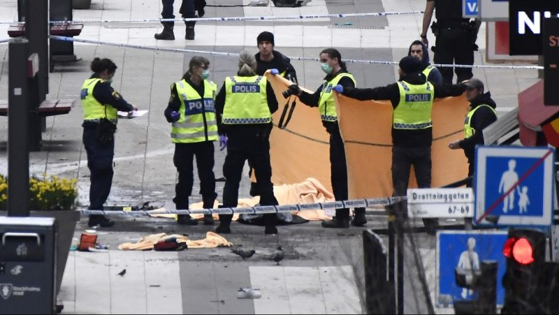 """Emergency services and police work at the scene where a truck crashed into the Ahlens department store at Drottninggatan in central Stockholm, April 7, 2017.  A truck slammed into a crowd of people outside a busy department store in central Stockholm on Friday, causing """"deaths"""" in what the prime minister described as an """"terror attack.""""  / AFP PHOTO / Jonathan NACKSTRAND / ALTERNATIVE CROP"""