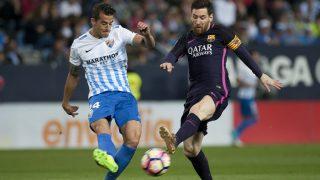 Malaga's defender Luis Hernandez (L) vies with Barcelona's Argentinian forward Lionel Messi during the Spanish league football match Malaga CF vs FC Barcelona at La Rosaleda stadium in Malaga on April 8, 2017. / AFP PHOTO / JORGE GUERRERO