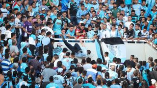 Fifth picture of a series of six displaying Belgrano's supporter Emanuel Balbo (C) falling from the stand of the Mario Kempes stadium after he was pushed by other supporters of the same team while trying to escape for the aggressions during half time of the Argentine First division football match derby between Belgrano and Talleres, in Cordoba, on April 15, 2017. Balbo is brain dead since he was thrown over the railing on Saturday when he recognized in the crowd the man who ran over and killed his brother four years before.  / AFP PHOTO / NICOLAS AGUILERA