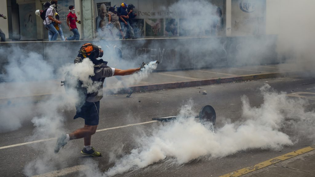 Demonstrators clash with the riot police during a protest against Venezuelan President Nicolas Maduro, in Caracas on April 20, 2017. Venezuelan riot police fired tear gas Thursday at groups of protesters seeking to oust President Nicolas Maduro, who have vowed new mass marches after a day of deadly unrest. Police in western Caracas broke up scores of opposition protesters trying to join a larger march, though there was no immediate repeat of Wednesday's violent clashes, which left three people dead. / AFP PHOTO / Ronaldo SCHEMIDT