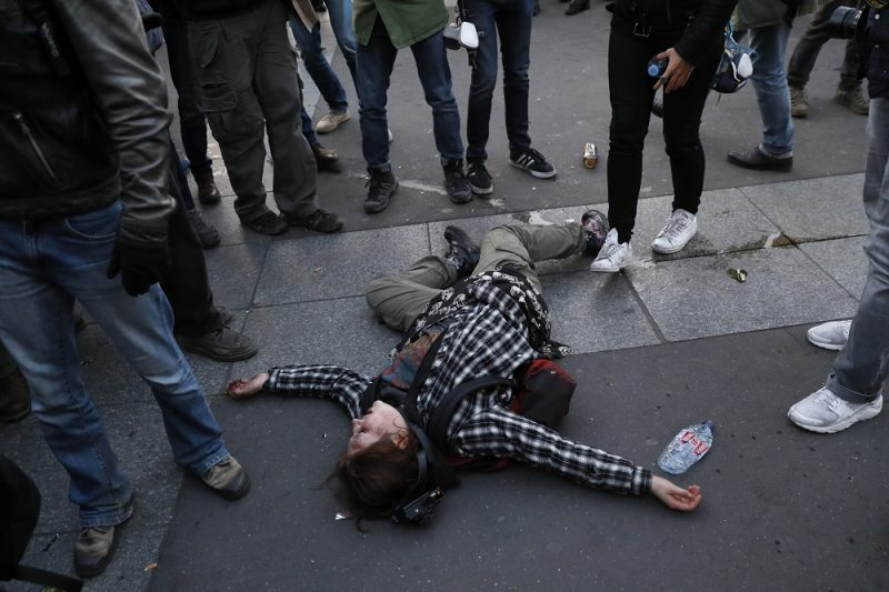 A wounded demonstrator lies on the ground during a demonstration called by anti-fascists in Paris on April 23, 2017 following the announcement of the results of the first round of the Presidential election. Centrist Emmanuel Macron finished ahead of far-right leader Marine Le Pen on Sunday to qualify alongside her for the runoff in France's presidential election, initial projections suggested.  / AFP PHOTO / THOMAS SAMSON