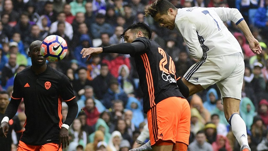 Real Madrid's Portuguese forward Cristiano Ronaldo (R) heads the ball to score a goal during the Spanish league football match Real Madrid CF vs Valencia CF at the Santiago Bernabeu stadium in Madrid on April 29, 2017. Cristiano Ronaldo added another record mark to an illustrious career by passing legendary English striker Jimmy Greaves to becoming the all-time top scorer in Europe's top five leagues against Valencia today.   / AFP PHOTO / PIERRE-PHILIPPE MARCOU