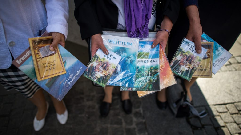 Members of the religious group 'Jehova's Witnesses' distribute their brochures inMunich,Germany, 27 July 2015. They are also offering Chinese-language versions of their booklets due to the many tourists from China. Photo: Matthias Balk/dpa