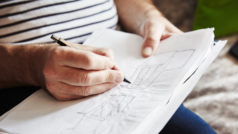 [England] A man seated using a pen and drawing sketches, a designer at work.