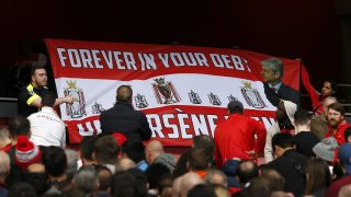 Supporters hold up a pro-Wenger banner in the crowd after the English Premier League football match between Arsenal and Manchester City at The Emirates in London, on April 2, 2017. The game finished 2-2. / AFP PHOTO / IKIMAGES / Ian KINGTON / RESTRICTED TO EDITORIAL USE. No use with unauthorized audio, video, data, fixture lists, club/league logos or 'live' services. Online in-match use limited to 45 images, no video emulation. No use in betting, games or single club/league/player publications.