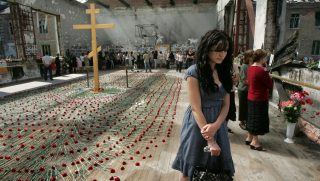 (FILES) This file photo taken on September 1, 2009 shows women mourning inside the Beslan school gymnasium  while commemorating the fifth anniversary of the 2004 terrorist hostage takeover that took the lives of over 330 people, including 186 children.  The European Court of Human Rights noted 'Serious failings' by Russia in Beslan massacre on April 13, 2017, and condamned Russia to pay 3 millions euros to the claimants, 409 victims or relatives of the Beslan tragedy during which around 30 heavily-armed gunmen held some 1,300 children and adults hostage for three days in the school in North Ossetia in 2004. / AFP PHOTO / KAZBEK BASAYEV