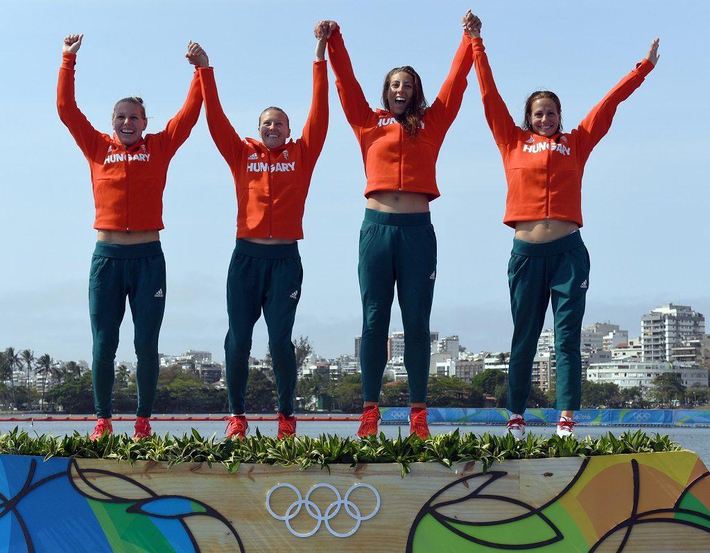 Hungary's Tamara Csipes, Hungary's Krisztina Fazekas-Zur, Hungary's Danuta Kozak and Hungary's Gabriella Szabo celebrate on the podium of the Women's Kayak Four (K4) 500m final at the Lagoa Stadium during the Rio 2016 Olympic Games in Rio de Janeiro on August 20, 2016. / AFP PHOTO / WILLIAM WEST