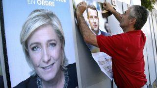 Bayonne, 2017. április 19.A francia elnökválasztáson független jelöltként induló Emmanuel Macron volt francia gazdasági miniszter kampányplakátját ragasztja falra egy férfi a délnyugat-franciaországi Bayonne városban 2017. április 19-én. Balról Marine Le Pen, a jobboldali Nemzeti Front (FN) elnöke és államfőjelöltje. Az elnökválasztás első fordulóját április 23-án rendezik. (MTI/AP/Bob Edme)
