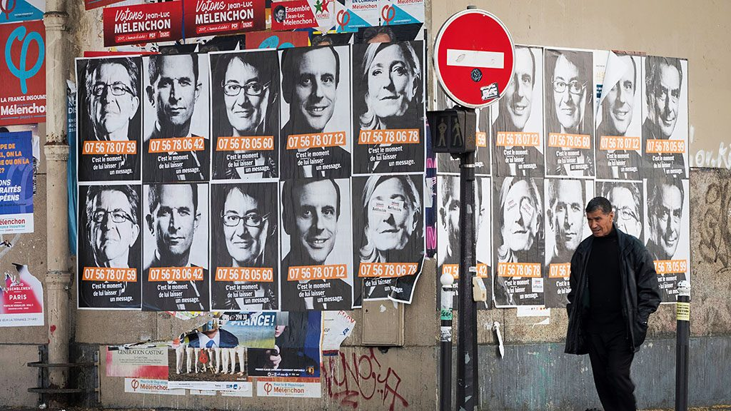 """This picture taken in Paris on April 19, 2017, shows posters of French presidential election candidates as part of a campaign of """"Solidarite Sida"""". / AFP PHOTO / JOEL SAGET"""