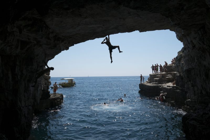 PULA, CROATIA - AUGUST 04:  A young man poses while he climbs in an 8 to 10 meter-high cave of Stoja on August 4, 2014 near Pula, Croatia. Deep Water Soloing (DWS), free climbing over water, is a relatively new discipline and is popular with climbers wanting to go rock climbing during the high summer temperatures. Climbing over deep water means most of the climbing routes are safe for beginners but still offer a challenge for the more advanced climber. There are many opportunities for DWS at the mile-long cliffs of Croatia.  (Photo by Thomas Lohnes/Getty Images)