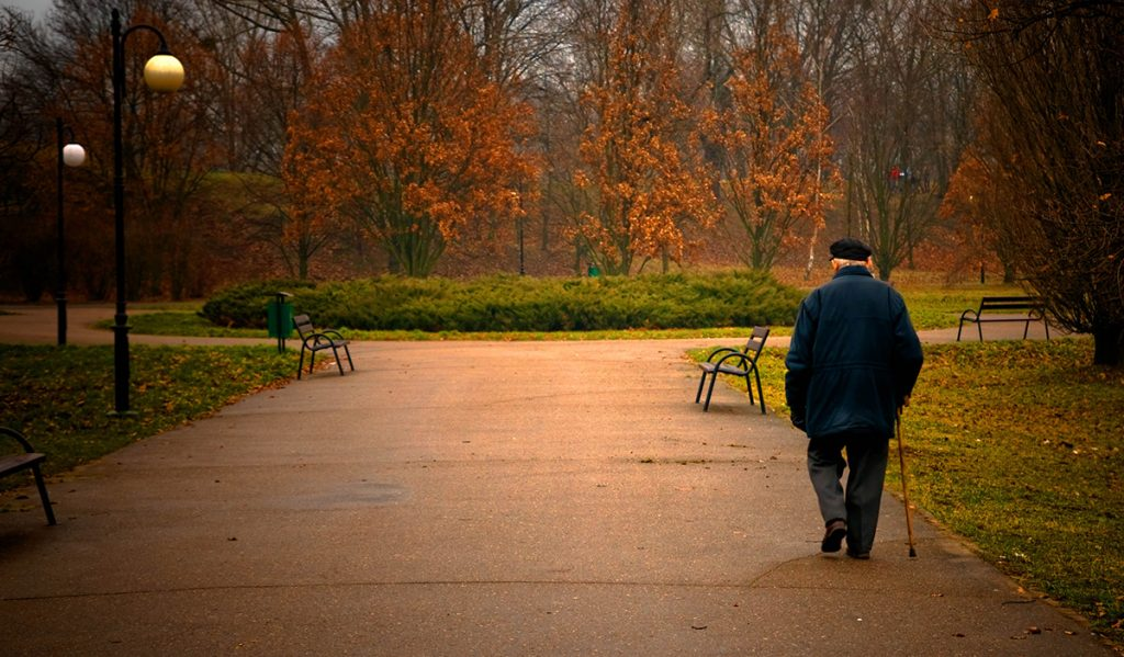 Old age concept. Man walks in autumn park