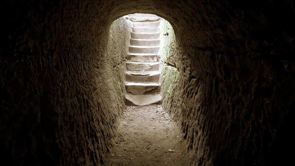 Light at the end of the tunnel. Dark stone room with a stairway encased in sunlight.