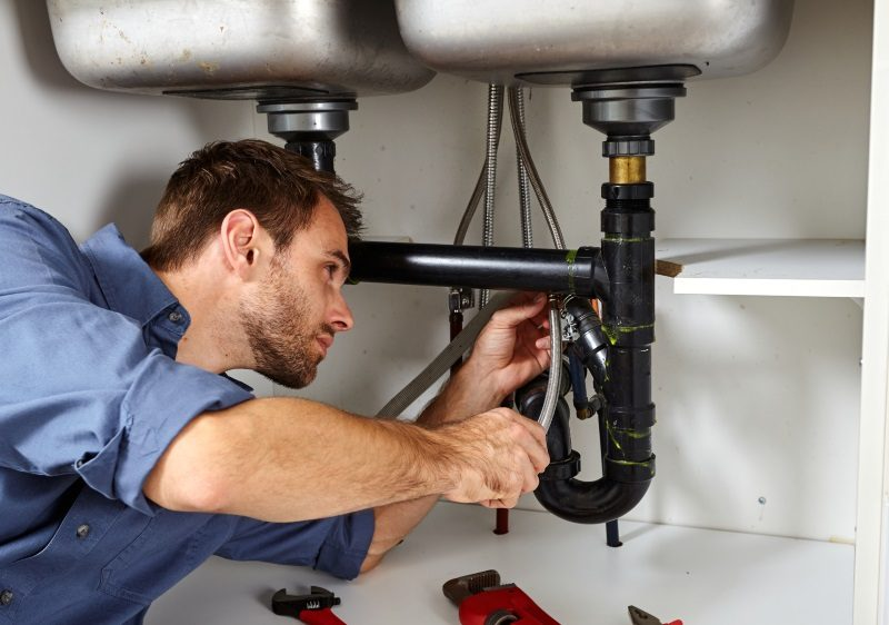 Plumber with tools doing reparation in the kitchen.