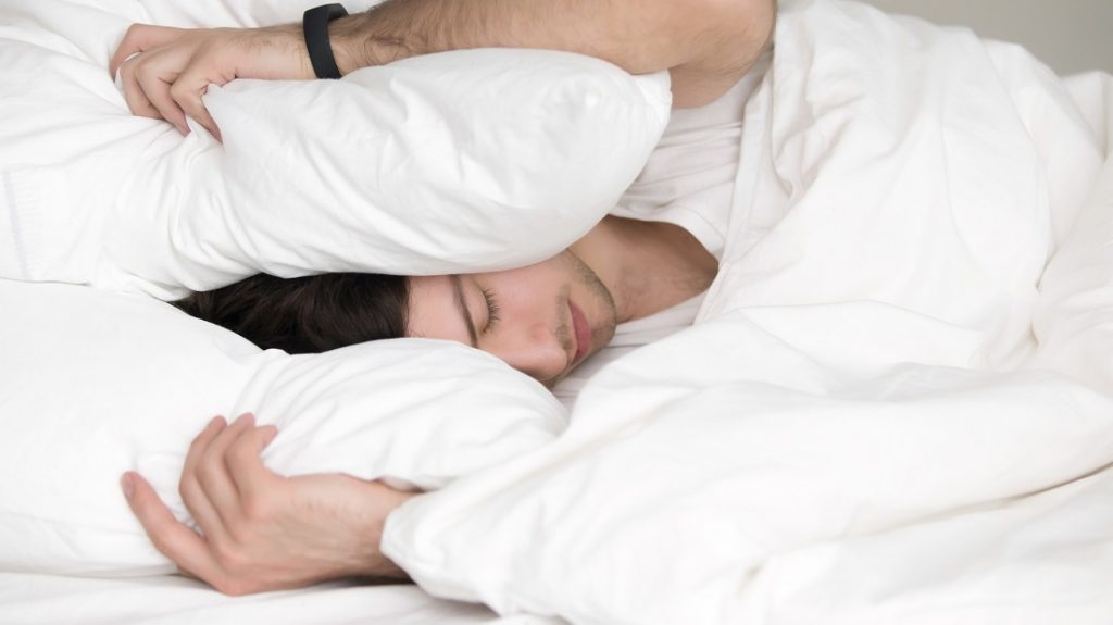 Too noisy to sleep. Handsome man covering his head and ears blocking out the sound with a pillow, suffering from loud alarm wake-up signal, young guy in bed awoken by a noise around him