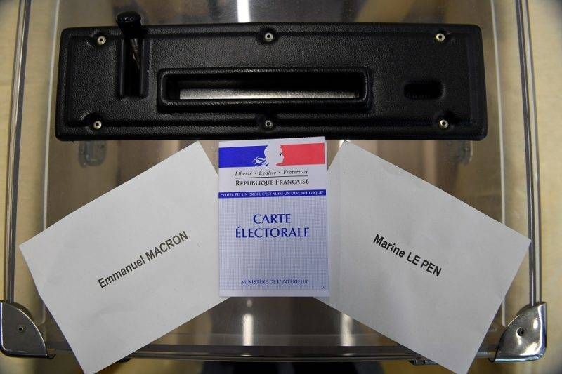 This picture, taken on May 5, 2017 an electoral card next to ballots for French presidential election candidate for the En Marche ! movement, Emmanuel Macron (L) and French presidential election candidate for the far-right Front National Marine Le Pen and on a ballot box at a polling station in  Rennes, western France, two days ahead of the second-round run-off of France's presidential election. / AFP PHOTO / DAMIEN MEYER