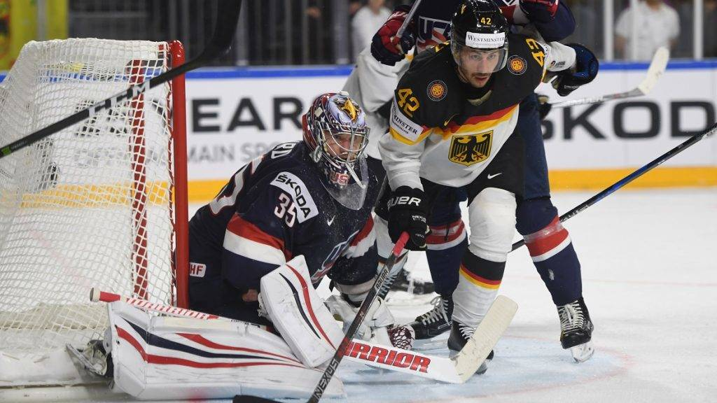 Germany´s Yasin Ehliz, US Jimmy Howard and Noah Hanifin vie for the puck  during the IIHF Ice hockey world championship first round match between USA and Germany in the LANXESS arena in Cologne on May 5, 2017. / AFP PHOTO / PATRIK STOLLARZ