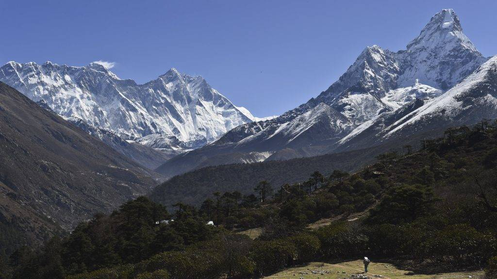 """(FILES) In this photograph taken on April 20, 2015, a Nepalese porter carries goods along a pathway in the Himalayas, with Mount Everest on the left, in the village of Tembuche in the Khumbu region of northeastern Nepal. An American climber died May 21, 2017 on his way to the summit of Mount Everest, expedition organisers said, the latest death to mar the ongoing climbing season. The 50-year-old mountaineer died close to the Balcony, a small platform above the 8,000-metre mark considered the mountain's """"death zone"""". / AFP PHOTO / ROBERTO SCHMIDT"""