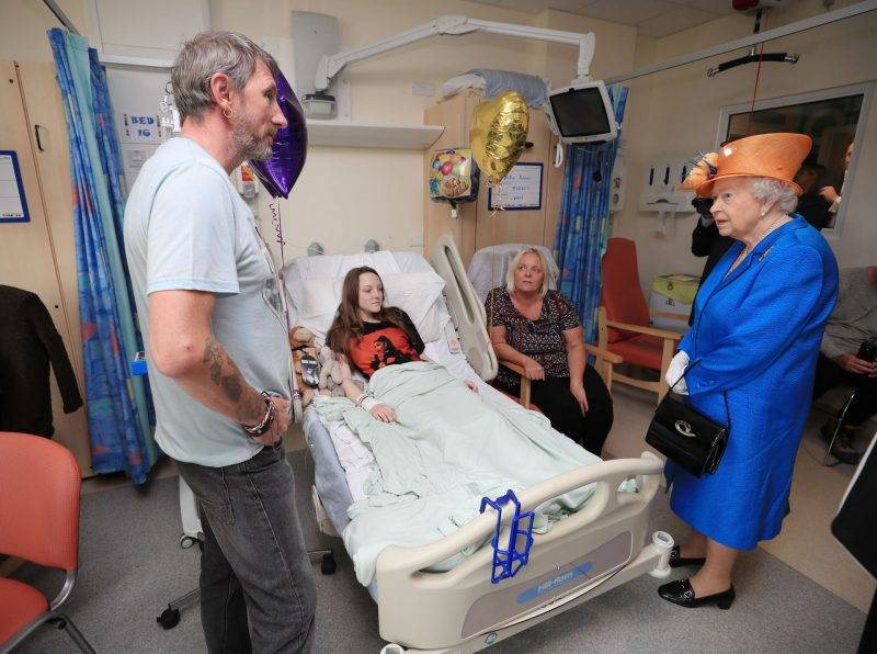 Britain's Queen Elizabeth II (R) speaks to Millie Robson, 15, from Co Durham (2L), who was injured in the May 22 Manchester Arena terror attack, her mother Marie (2R) and father David (L) during a visit to the Royal Manchester Children's Hospital in Manchester, northwest England, on May 25, 2017 to meet injured victims of the terror attack and to thank members of staff who treated them. / AFP PHOTO / POOL / Peter Byrne
