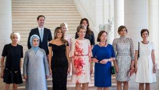 (Front row LtoR) Brigitte Macron, wife of French President, Emine Gulbaran Erdogan, wife of Turkey's President, First Lady of the US Melania Trump, Queen Mathilde of Belgium, Stoltenberg's wife Ingrid Schulerud, partner of Bulgaria's President Desislava Radeva, partner of Charles Michel Amelie Derbaudrenghien, (back row, LtoR), husband of Luxembourg's prime minister Gauthier Destenay, partner of Slovenia's Prime Minister Mojca Stropnik and wife of Iceland's President Thora Margret Baldvinsdottir pose for a family photo before a diner  at the Royal castle in Laken/Laeken, on May 25, 2017, in Brussels. / AFP PHOTO / Aurore Belot
