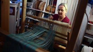 Helen Hanisch sits at her weaving loom at the Christmas Market 'WeihnachtsZauber' at Gendarmenmarkt in Berlin, Germany, 21 November 2016. The market is open from 21 NOvember until 31 December 2016. PHOTO: BRITTA PEDERSEN/dpa