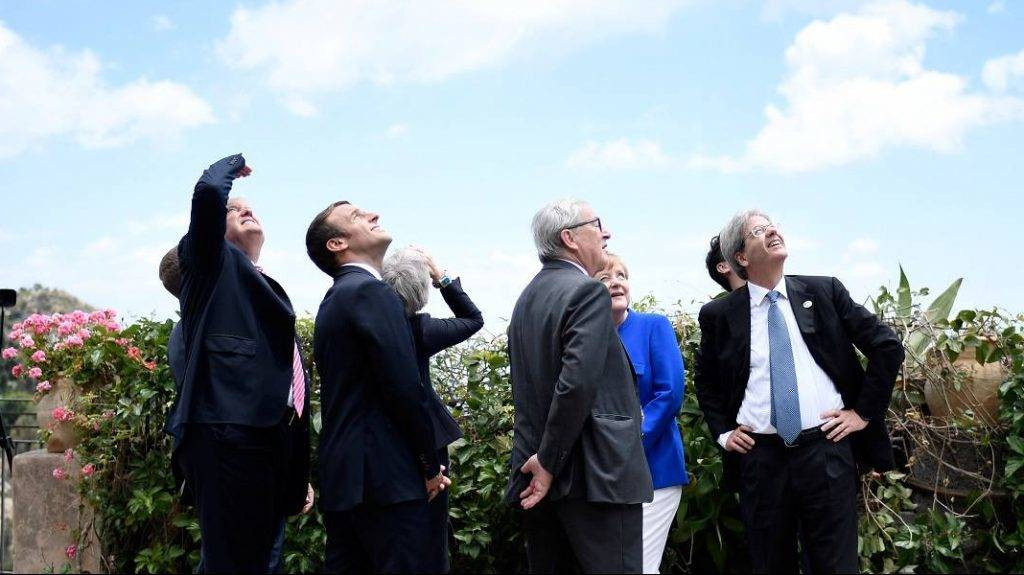 (L-R) US President Donald Trump, French President Emmanuel Macron, Britain's Prime Minister Theresa May, the President of the European Commission Jean-Claude Juncker, German Chancellor Angela Merkel and Italian Prime Minister Paolo Gentiloni watch an Italian flying squadron during the Summit of the Heads of State and of Government of the G7, the group of most industrialized economies, plus the European Union, on May 26, 2017 in Taormina, Sicily. The leaders of Britain, Canada, France, Germany, Japan, the US and Italy will be joined by representatives of the European Union and the International Monetary Fund (IMF) as well as teams from Ethiopia, Kenya, Niger, Nigeria and Tunisia during the summit from May 26 to 27, 2017. / AFP PHOTO / POOL / STEPHANE DE SAKUTIN