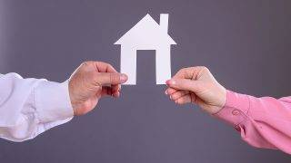 Male and female hands holding a paper house