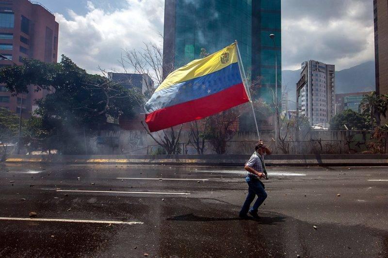 Caracas, 2017. április 27.Nemzetiszínű zászlót visz egy tüntető a Nicolás Maduro elnök vezette szocialista kormány elleni tiltakozáson, Caracasban 2017. április 26-án. (MTI/EPA/Miguel Gutierrez)