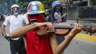 Caracas, 2017. május 9.Maszkos tüntető hegedül a Nicolás Maduro venezuelai elnök és szocialista kormánya elleni tiltakozáson Caracasban 2017. május 8-án. Április eleje óta mindennaposak a tüntetések Venezuelában, a biztonsági erők és a tüntetők közötti összecsapásokban eddig legkevesebb harminchatan vesztették életüket. (MTI/EPA/Christian Hernández)