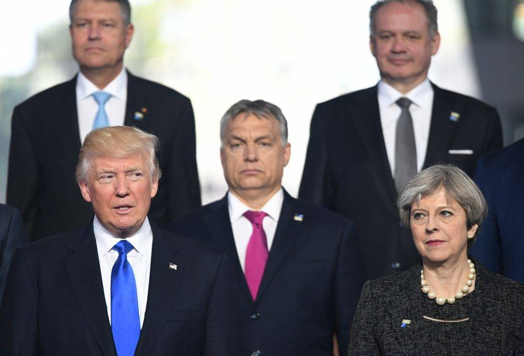(L-R) US President Donald Trump, Hungarian Prime Minister Viktor Orban and British Prime Minister Theresa May, pose for a family picture during the NATO (North Atlantic Treaty Organization) summit at the NATO headquarters, in Brussels, on May 25, 2017.  / AFP PHOTO / POOL / Stefan Rousseau