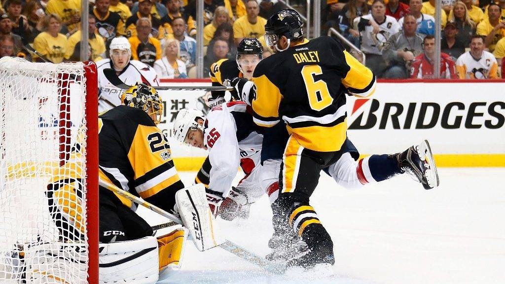 PITTSBURGH, PA - MAY 01: Andre Burakovsky #65 of the Washington Capitals tries to get a shot off on goalie Marc-Andre Fleury #29 of the Pittsburgh Penguins while taking a check from Trevor Daley #6 during the first period in Game Three of the Eastern Conference Second Round during the 2017 NHL Stanley Cup Playoffs at PPG Paints Arena on May 1, 2017 in Pittsburgh, Pennsylvania.   Gregory Shamus/Getty Images/AFP