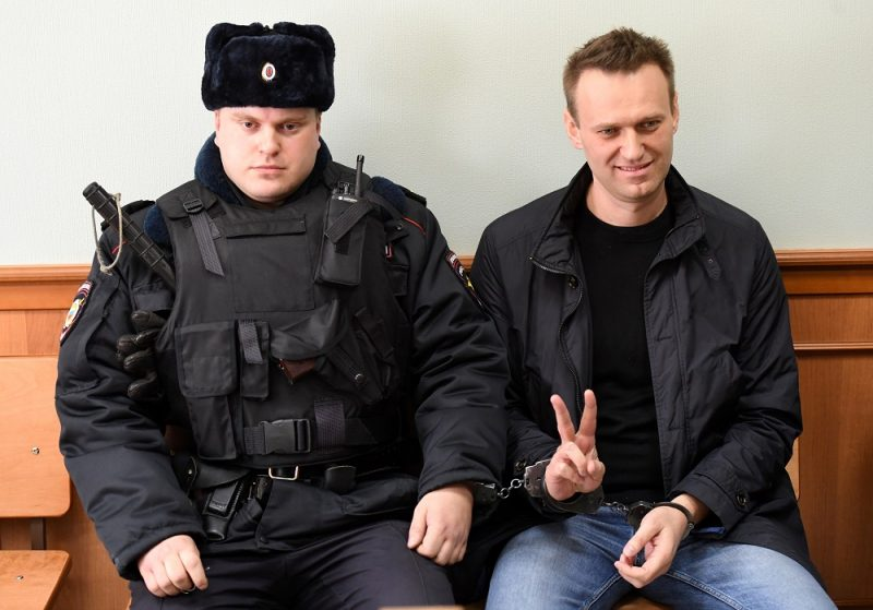 Kremlin critic Alexei Navalny, who was arrested during March 26 anti-corruption rally, shows a v-sign during an appeal hearing at a court in Moscow on March 30, 2017. A Russian court on March 27 sentenced Kremlin critic Alexei Navalny to 15 days behind bars after ruling that he had resisted police during a massive anti-corruption protest Sunday in Moscow. / AFP PHOTO / Kirill KUDRYAVTSEV