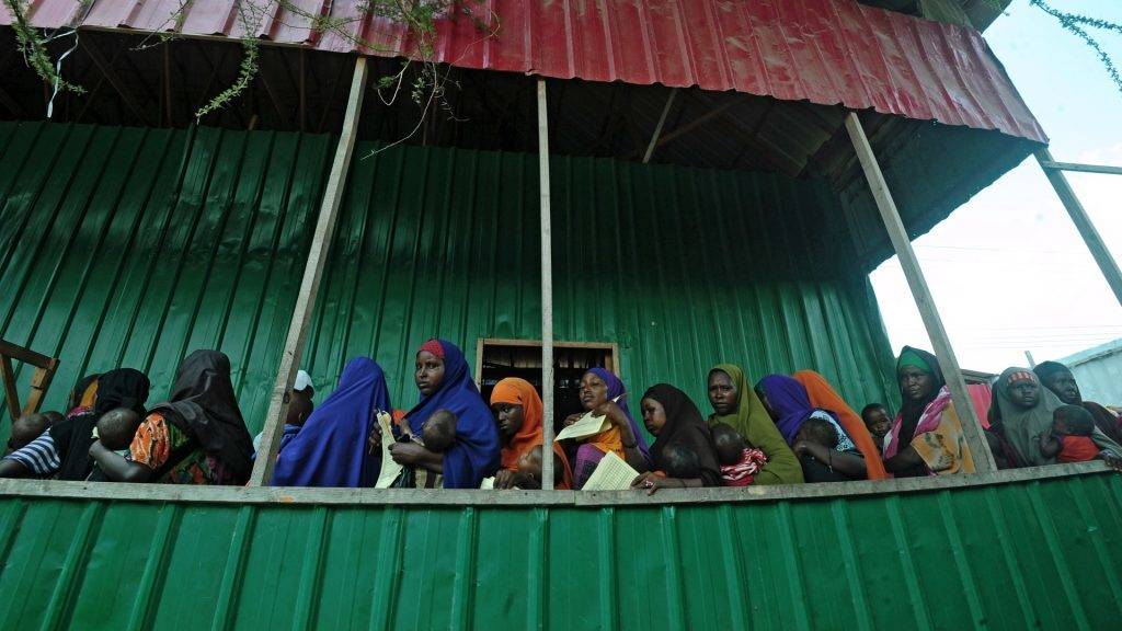 """Newly displaced Somali women queue with their malnourished children as they try to receive medical treatment on outskirts of Mogadishu on April 11, 2017.  The United Nations warned on April 11 of a growing risk of mass deaths from starvation among people living in conflict and drought-hit areas of the Horn of Africa, Yemen and Nigeria. UNHCR's operations in famine-hit South Sudan, and in Nigeria, Somalia and Yemen, which are on the brink of famine, are funded at between just three and 11 percent, said UN refugee agency spokesman Adrian Edwards, as the UN faces a """"severe"""" funding shortfall to help people affected by famine. / AFP PHOTO / MOHAMED ABDIWAHAB"""