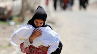 A displaced Iraqi woman carries a baby as she evacuates from western Mosul's Zanjili neighbourhood on June 1, 2017 during ongoing battles between Iraqi forces to retake the city from Islamic State (IS) group fighters. / AFP PHOTO / KARIM SAHIB