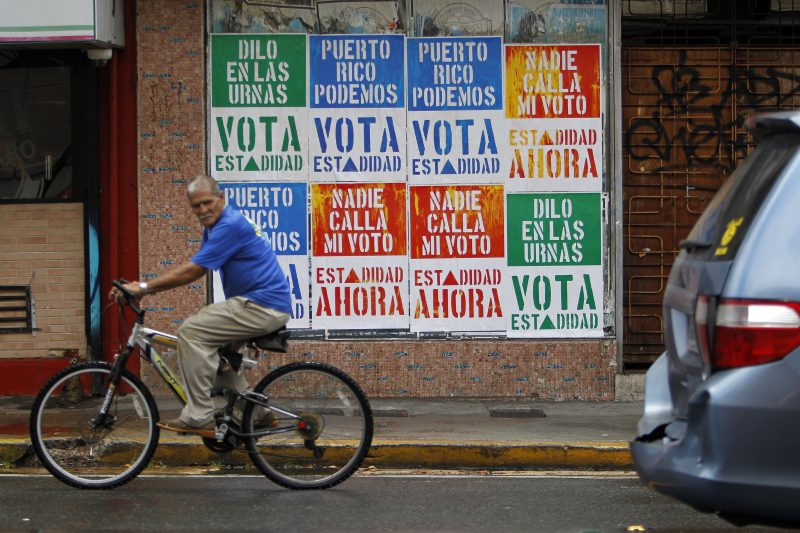 A rides his bicycle in front of a wall covered with campaign posters promoting Puerto Rico's statehood in San Juan, on June 9, 2017. A referendum on the political status of the US territory takes place on June 11, 2017. The US commonwealth of Puerto Rico votes on whether to become the 51st state. / AFP PHOTO / Ricardo ARDUENGO