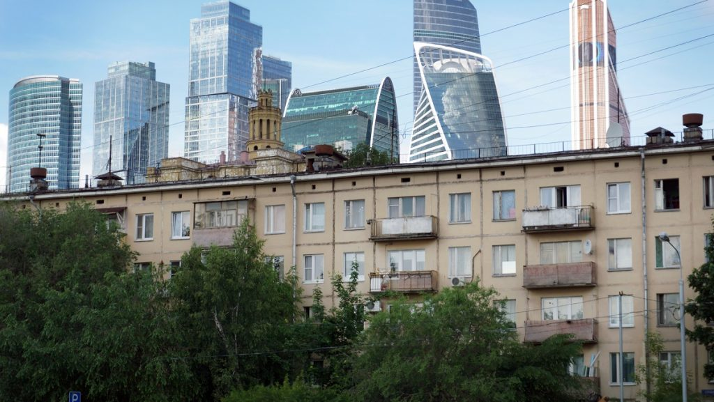 Skyscrapers of the Moscow City business centre (Moskva City) are seen behind a five-storey building dating from the 1960s in western Moscow on June 11, 2017. The controversial plan to knock down Soviet-era apartment blocks and redevelop the old neighbourhoods announced in February by Moscow mayor Sergei Sobyanin has led to an outcry as many residents say the programme is a ploy to funnel state funds into construction companies while moving them to housing with lower market value.  / AFP PHOTO / Alexander NEMENOV