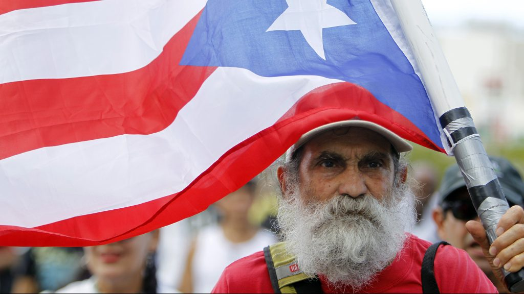A man carries a Puerto Rican flag during a protest against the referendum for Puerto Rico political status in San Juan, on June 11, 2017. To become a true US state, to choose independence or to maintain the status quo: Puerto Ricans went to the polls to consider their political future in a non-binding referendum many have vowed to boycott. / AFP PHOTO / Ricardo ARDUENGO