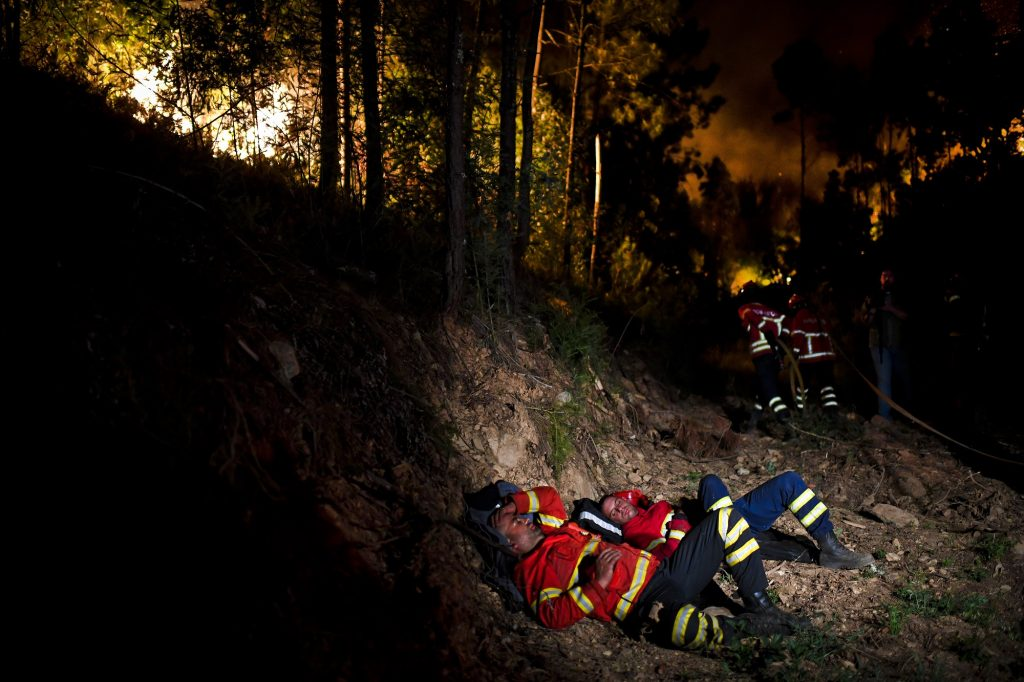 Firefighters rest during a wildfire at Penela, Coimbra, central Portugal, on June 18, 2017.  A wildfire in central Portugal killed at least 25 people and injured 16 others, most of them burning to death in their cars, the government said on June 18, 2017. Several hundred firefighters and 160 vehicles were dispatched late on June 17 to tackle the blaze, which broke out in the afternoon in the municipality of Pedrogao Grande before spreading fast across several fronts.  / AFP PHOTO / PATRICIA DE MELO MOREIRA