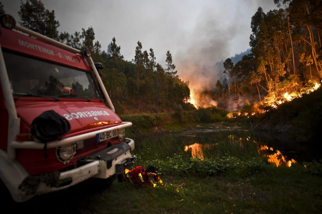 A firefighter rests next to fire combat truck during a wildfire at Penela, Coimbra, central Portugal, on June 18, 2017.  A wildfire in central Portugal killed at least 25 people and injured 16 others, most of them burning to death in their cars, the government said on June 18, 2017. Several hundred firefighters and 160 vehicles were dispatched late on June 17 to tackle the blaze, which broke out in the afternoon in the municipality of Pedrogao Grande before spreading fast across several fronts.    / AFP PHOTO / PATRICIA DE MELO MOREIRA