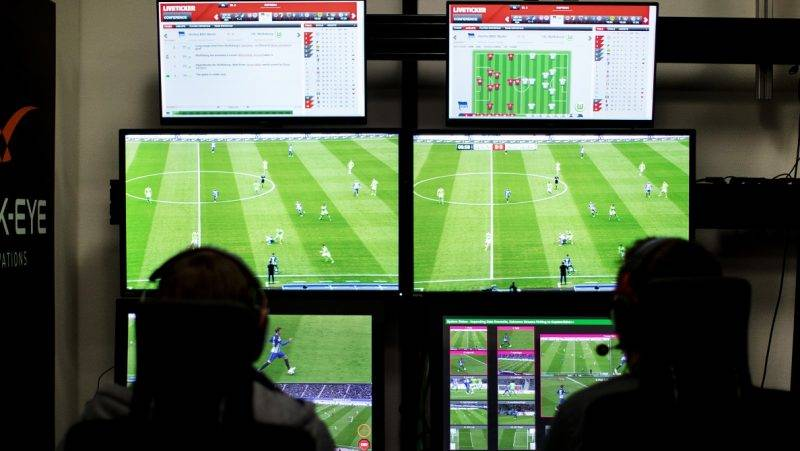 A referee and a cameraman sit in front of several screens on which German Bundesliga soccer games are being displayed in Cologne, Germany, 22 April 2017. Photo: Marcel Kusch/dpa