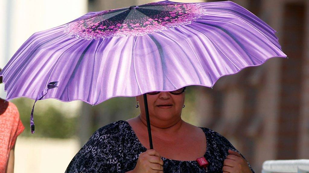 PHOENIX, AZ - JUNE 20: A Phoenix resident uses an umbrella to find some relief from the sun on June 20, 2017 in Phoenix, Arizona. Record temperatures of 118 to 120 degrees were expected on Tuesday for the Phoenix-metro area.   Ralph Freso/Getty Images/AFP