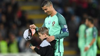 Portugal's forward Cristiano Ronaldo speaks to a child after the FIFA World Cup 2018 qualification football match between Latvia and Portugal in Riga, on June 9, 2017. / AFP PHOTO / JANEK SKARZYNSKI