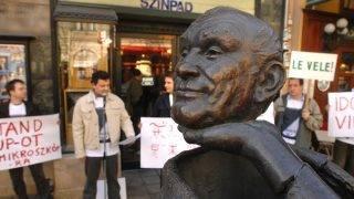 """Budapest, 2009. április 1. Varga Ferenc József a Mikroszkóp Színpad humoristája beszédet mond a színpad elõtt Hofi Géza szobránál. A demonstráción felolvastak egy 12 pontból álló petíciót, amely """"hadat üzen"""" a régi rossz vicceknek, és """"követeli"""" az elõre hozott választásokat, valamint a stand up mûfaj visszatérését a színházba. Április 8-án a Mikroszkóp színpadon útjára indul a stand up-szerdák sorozata. MTI Fotó: Kollányi Péter"""
