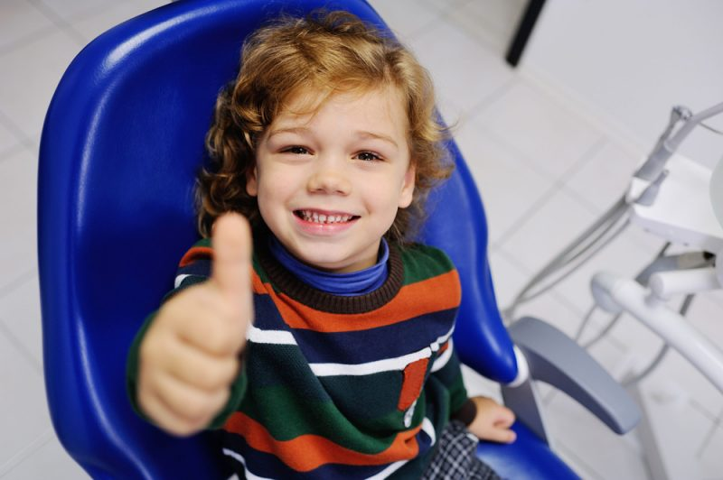 66533440 - baby boy with curly red hair in blue dental chair. children's dentist