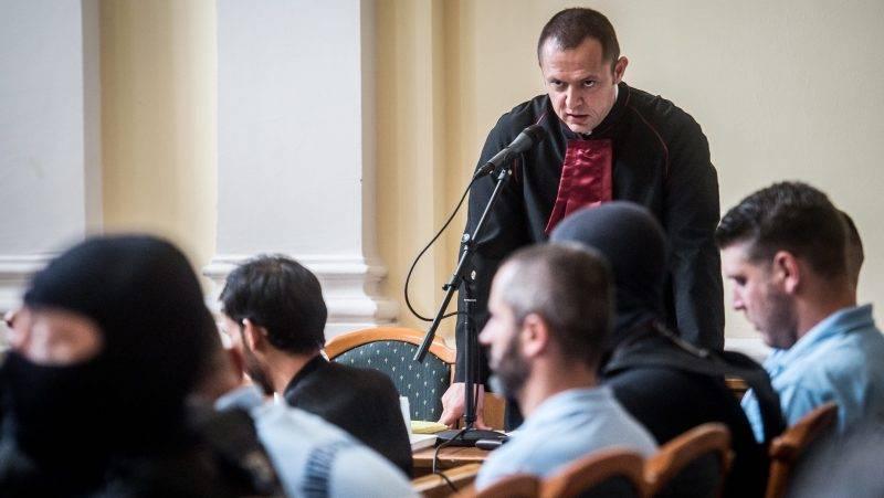 """Kecskemét, 2017. június 21.  Az ügyész ismerteti a vádat a """"parndorfi ügyként"""" elhíresült, 71 ember halálát okozó eset tárgyalásán a Kecskeméti Törvényszék tárgyalótermében 2017. június 21-én. A Bács-Kiskun Megyei Főügyészség embercsempészés és más bűncselekmények miatt emelt vádat 1 afgán, 9 bolgár, illetve 1 bolgár és libanoni, kettős állampolgárságú férfi ellen 2017 májusa elején. A vád szerint a bűnszervezet tagjai 2015. augusztus 26-án hajnalban 71 embert zártak be egy belülről nem nyitható, sötét, szellőzés nélküli hűtőkamionba. A Kecskemétről a határra tartó hűtőkocsiban 59 férfi, 8 nő és 4 gyermek az indulástól számított három órán belül, még magyar területen, gyötrelmes körülmények között megfulladt. MTI Fotó: Ujvári Sándor"""